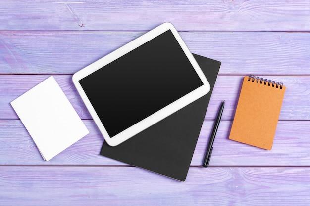 Digitaal tablet en blocnotekantoor op paars