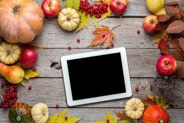 Digitaal tablet met gele esdoornbladeren, rode appels en pompoenen
