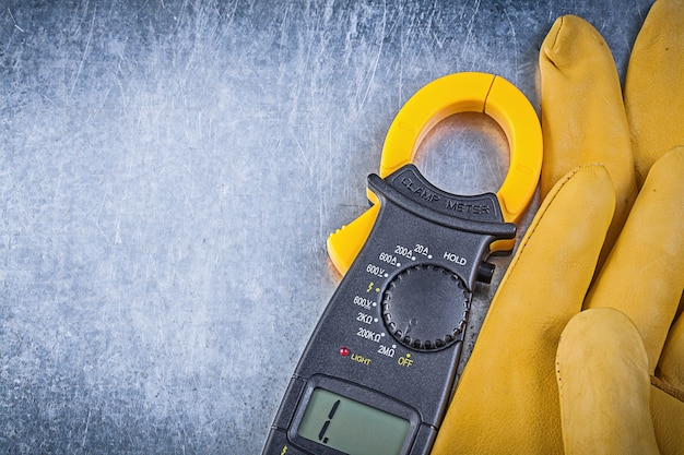 Digitale ampèremeter beschermende handschoenen op metalen achtergrond