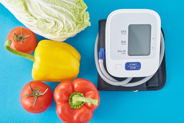 Digitale bloeddrukmeter en verse groenten op blauwe achtergrond. gezondheidszorg concept