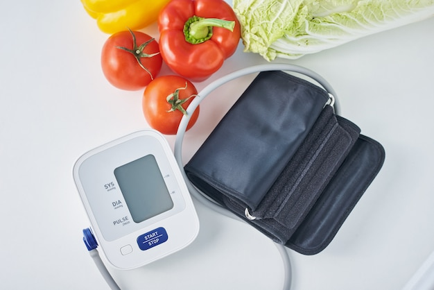 Digitale bloeddrukmeter en verse groenten op tafel. gezondheidszorg concept