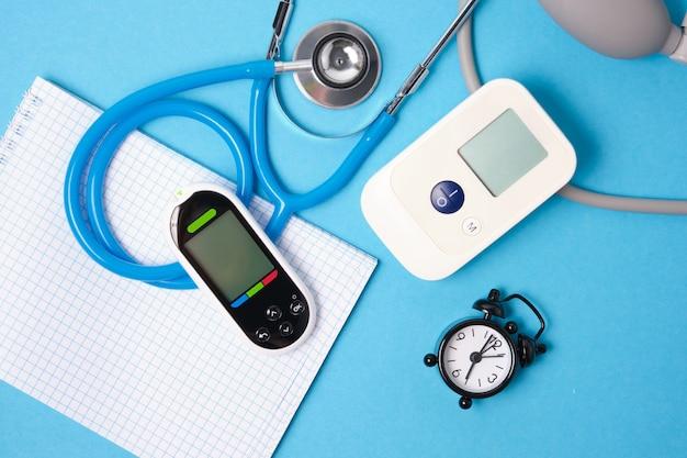 Digitale bloeddrukmeter, glucometer, stethoscoop, blocnote en wekker op blauwe achtergrond