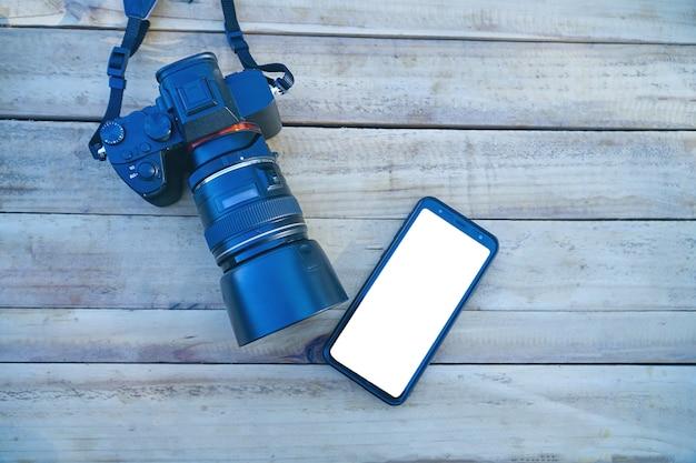 Digitale camera en smartphone op houten achtergrond technologie ontwikkelingsconcept. bovenaanzicht.