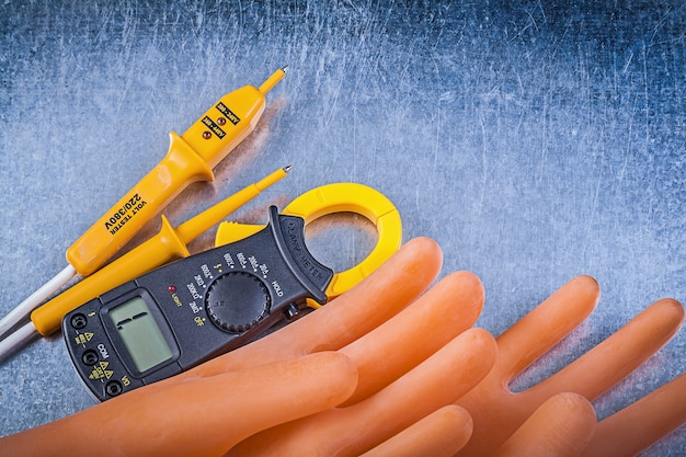 Digitale diëlektrische rubberen handschoenen van de ampèremeter elektrische tester op metaallijst, elektriciteitsconcept