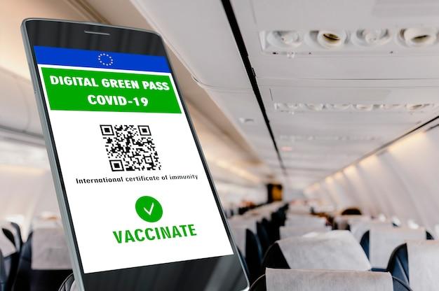 Digitale groene pas van de europese unie met de qr-code op een mobiel scherm, interieurachtergrond van een vliegtuig. covid-19 immuniteit. reis zonder beperkingen.