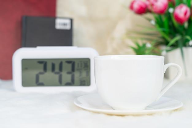Digitale klok en kopje koffie