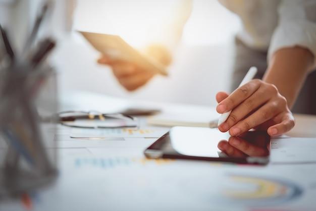 Digitale marketing, zakenman die digitale tablet en documenten op bureauachtergrond gebruiken.