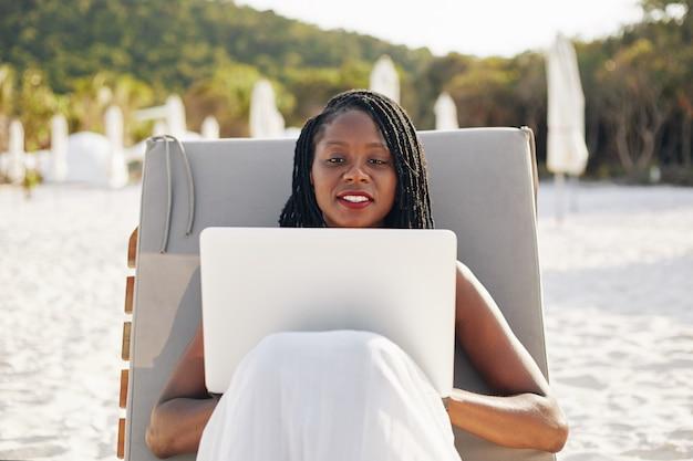 Digitale nomade die op strand werkt