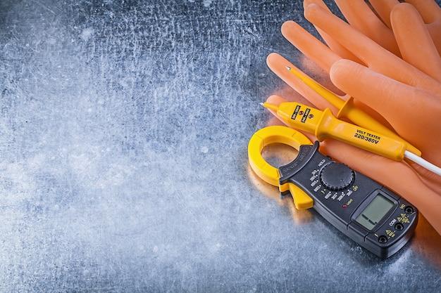 Digitale stroomtang elektrische tester isolerende handschoenen op metalen achtergrond elektriciteit concept
