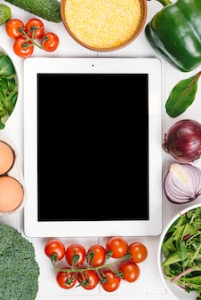 Digitale tablet die met groenten op wit bureau wordt omringd
