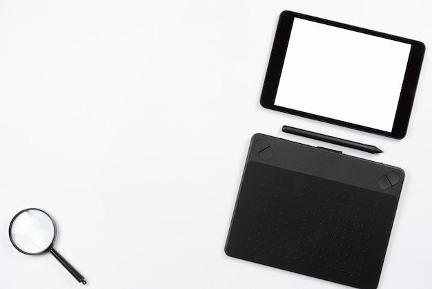 Digitale tablet en grafische digitale tablet met stylus en vergrootglas op witte achtergrond