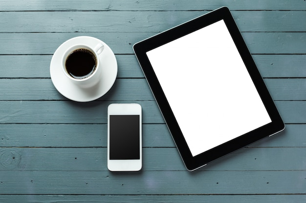 Digitale tablet en koffiekop op houten lijst
