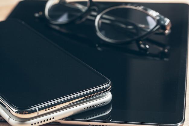 Digitale tablet en mobiele telefoon. de elektronische apparaten op houten lijst, sluiten omhoog.
