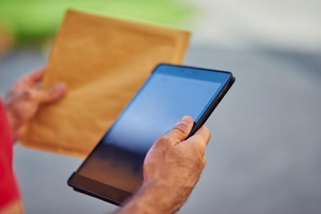 Digitale tablet en papieren pakket in handen