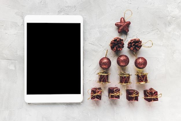 Digitale tablet en rode kerstversiering op de werkruimte van het bureau, grijze achtergrond. winter winkelen, feest, takenlijst, afstandsonderwijs, levensstijlconcept. bovenaanzicht, mock-up, kopieer ruimte