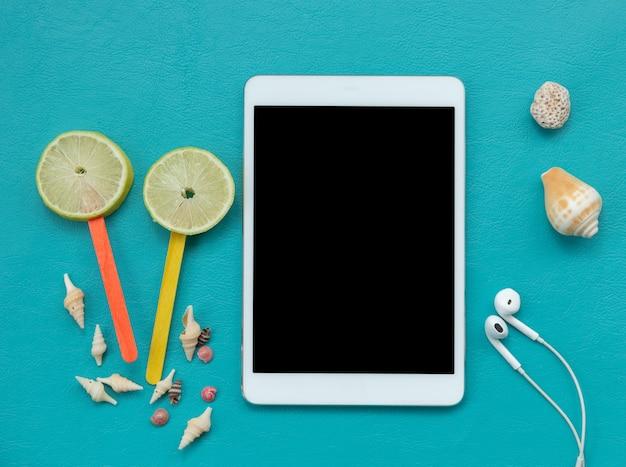 Digitale tablet en zomer elementen op blauw