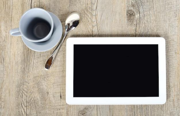 Digitale tablet met een kopje koffie