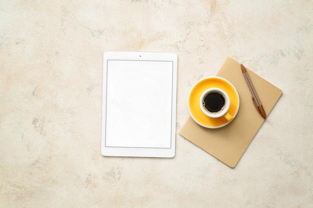 Digitale tablet met leeg scherm en kopje koffie, bovenaanzicht