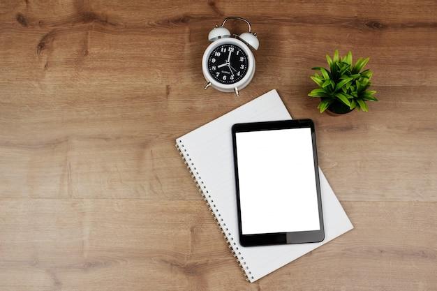 Digitale tablet met leeg scherm en notitieboekje op houten bureau