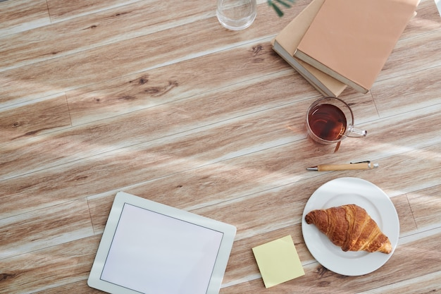 Digitale tablet met leeg scherm, thee met gebak en stapel boeken op tafel van creatieve student, van bovenaf bekijken