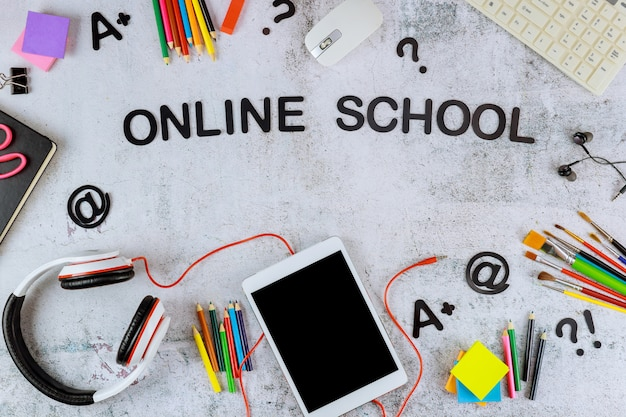 Digitale tablet met zwart mockup-scherm voor schoolonderwijs en kunstbenodigdheden op witte achtergrond.