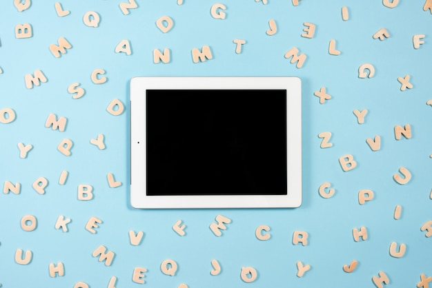 Digitale tablet met zwarte die schermvertoning met houten brieven op blauwe achtergrond wordt omringd