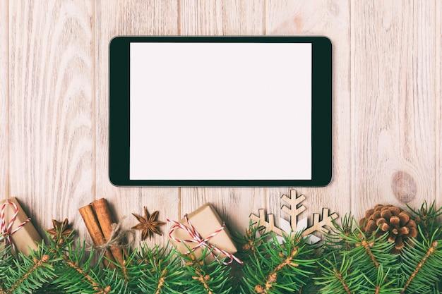 Digitale tablet mock up met rustieke kerst houten decoraties voor app-presentatie.
