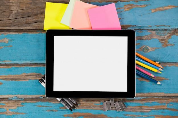 Digitale tablet op pennen, nietjes, kleurpotloden en plaknotities