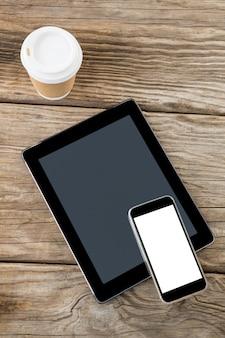 Digitale tablet, smartphone en wegwerp koffiekopje op houten tafel