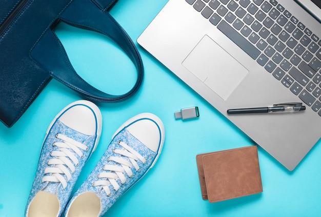 Digitale technologie en modieuze damesaccessoires op een blauwe achtergrond: laptop, usb stick, tas, portemonnee, sneakers, tas. bovenaanzicht plat liggen.