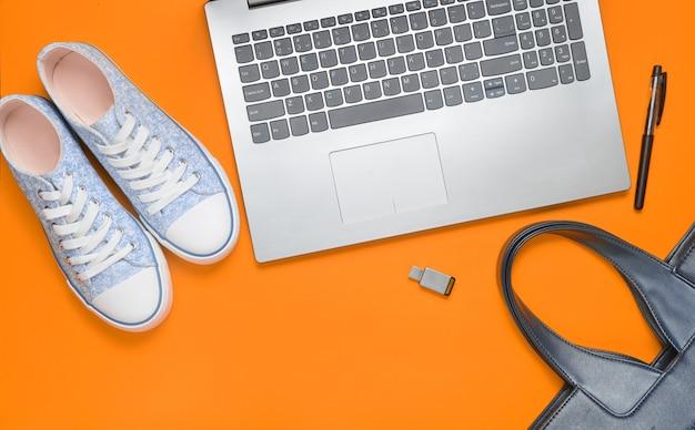 Digitale technologie en modieuze damesaccessoires op een oranje achtergrond: laptop, usb-stick, tas, sneakers, tas. bovenaanzicht plat liggen.