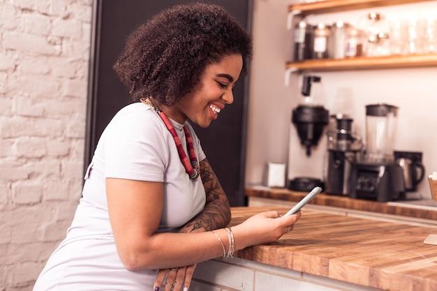 Digitale technologie. vrolijke gelukkige vrouw met behulp van haar smartphone zittend in het café