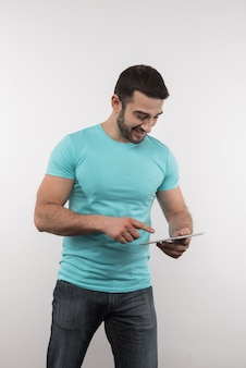 Digitale technologie. vrolijke man die tegen een witte achtergrond staat tijdens het gebruik van een tablet