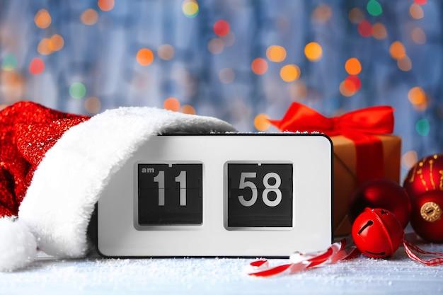 Digitale wekker met kerstmuts en decoraties tegen onscherpe lichten