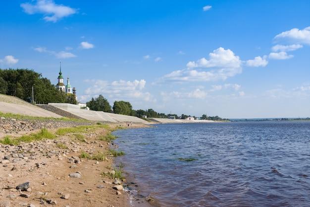 Dijk van de rivier de suhona en de kerk van st. nicolas in de zomer. veliky ustyug. rusland
