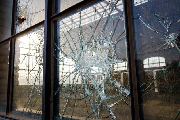 Dik gebroken glas van een raam in een verlaten industriële zone.