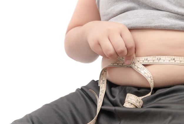 Dik kind bekijk zijn lichaamsvet met een meetlint