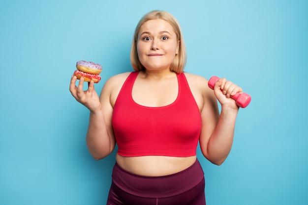 Dik meisje denkt donuts te eten in plaats van sportschool. concept van besluiteloosheid en twijfel