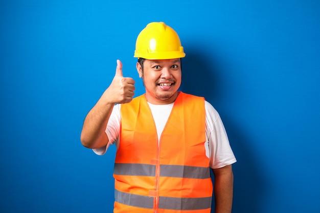 Dikke aziatische bouwvakker met een oranje veiligheidsvest en helm met een duim omhoog teken glimlachend Premium Foto