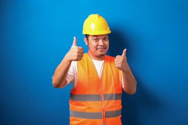 Dikke aziatische bouwvakker met een oranje veiligheidsvest en helm met een duim omhoog teken glimlachend
