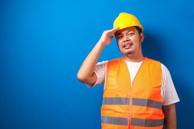 Dikke aziatische bouwvakker met een veiligheidshelm gestrest met de hand op het hoofd