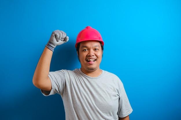 Dikke aziatische man met een helm die naar de camera kijkt terwijl hij zijn handen op elkaar klemt. de man toonde een gebaar van overwinning