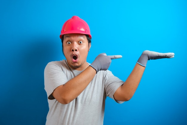 Dikke aziatische man met een helm presenteert iets in zijn hand terwijl hij zijwaarts kijkt. de man toonde een uitdrukking van vreugde en verbazing