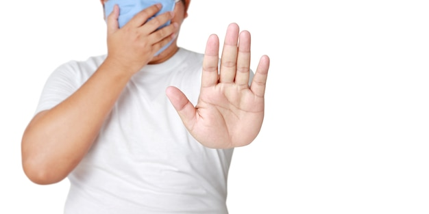 Dikke aziatische man met een masker steek je hand op, benader niet behoud sociale afstand. coronavirus-beschermingsconcept infectie verminderen voorkom de verspreiding van ziektekiemen. uitknippad. witte achtergrond