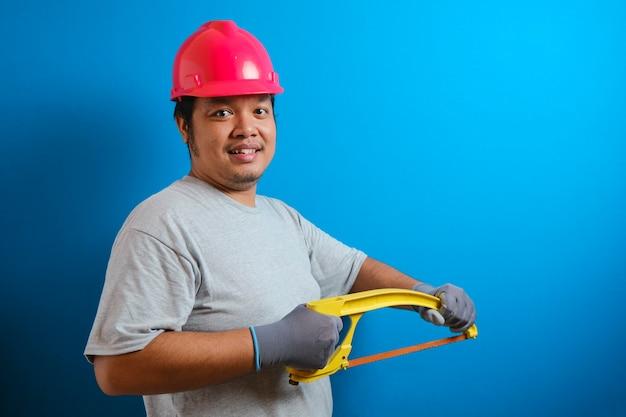 Dikke aziatische man met een rode helm glimlacht naar de camera terwijl hij een ijzerzaag vasthoudt. de man toonde vertrouwen