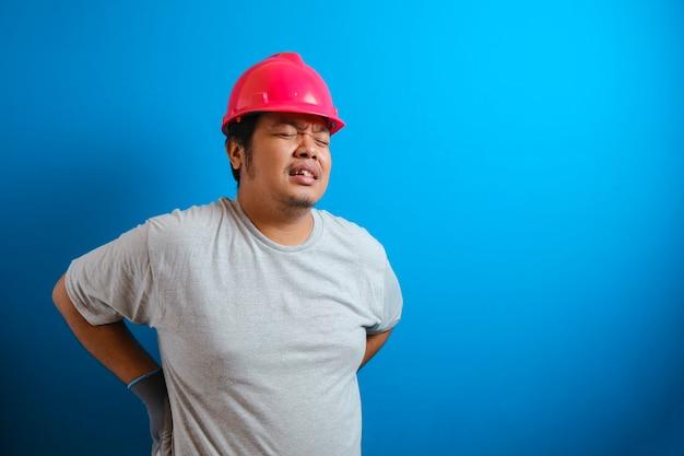 Dikke aziatische man met een rode helm voelt pijn in zijn rug. de man houdt zijn rug vast terwijl hij de pijn verdraagt