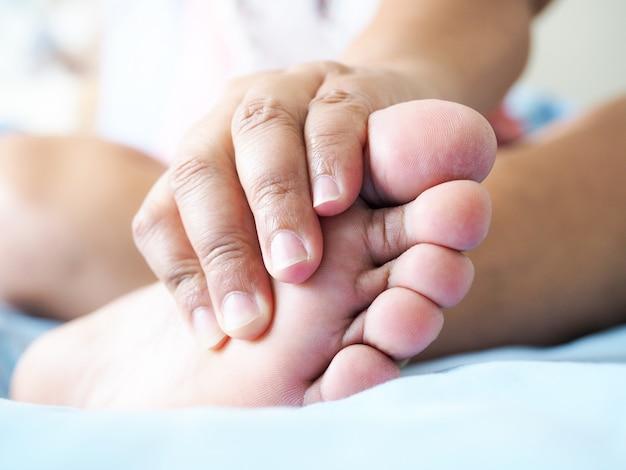 Dikke aziatische mensen gebruiken handen om de voeten te masseren tegen pijn in voetspieren en zenuwpijn.
