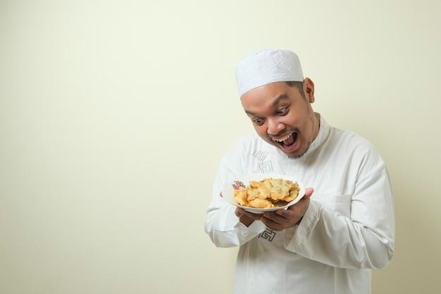 Dikke aziatische moslimmannen hebben erge honger en willen direct gefrituurd eten bij het verbreken van het vasten in de maand ramadan. de man toonde een blij gebaar
