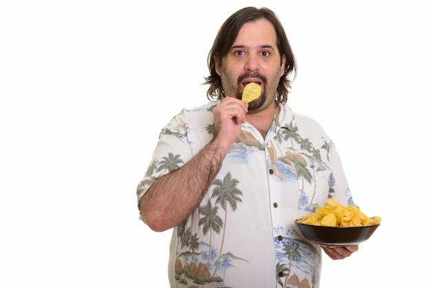 Dikke bebaarde blanke man chips eten geïsoleerd op wit