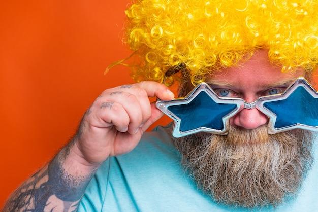 Dikke bedachtzame man met baardtattoos en zonnebril twijfelt ergens over